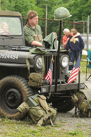 Patrick Parker,  curator of the Raleigh County Veteran's Museum, leans on a Jeep in a uniform from the Americal division as the crowd listens to speakers at the Memorial Day service held in Coal City. Jon C. Hancock/for The Register-Herald