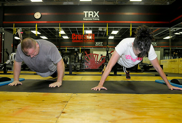 Thomas Stalnaker, left, and Sherri Thomas grind through a series of pushups during a CrossFit session at L.A. East Fitness on Appalachian Drive July 15. Brad Davis/The Register-Herald