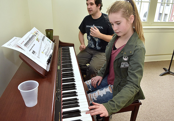 (Brad Davis/The Register-Herald) Teagan Sweeney, 11, gets a free piano lesson from School of Harmony instructor Ben Casto guides her through the basics during yesterday's Small Business Saturday event.
