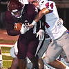 Matthew Moore, of Woodrow Wilson, left, plows ahead for some yardage against, Preston Harman, of Morgantown, in the first half during game held at Woodrow Wilson High School.<br /> (Rick Barbero/The Register-Herald)