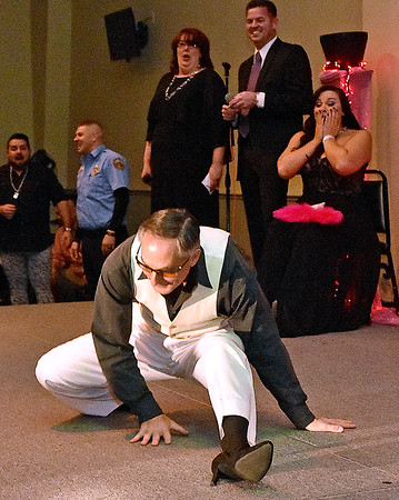 (Brad Davis/The Register-Herald) Participant Stan Seldon not only wow spectators, but also shocks the emcees and others backstage as he drops into a split while dancing on stage during the annual Hunks in Heels fundraising event for the Women's Resource Center Friday night at the Beckley Moose Lodge.