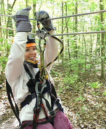 Rina Nehdar, of Los Angeles, member of the Freelance Council of the Society of American Travel Writers, zipping during the TreeTops Zipline Canopy Tours at Adventure On The Gorge Wednesday morning. Forty-one Travel Writers are exploring and writing about West Virginia this week.<br /> (Rick Barbero/The Register-Herald)