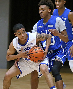 (Brad Davis/The Register-Herald) Mid-State Ford's (Class AAA) Justin Phillips looks for an open teammate as he tries to hold off EIN's (National) Mikey Penn during the Scott Brown Classic Saturday night at the Beckley-Raleigh County Convention Center.