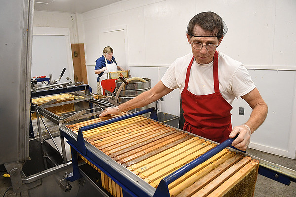 Terri Giles and Michael Deckner, Appalachian Headwaters,  begin the extracting process for making honey at Camp Waldo in Hinton<br /> (Rick Barbero/The Register-Herald)