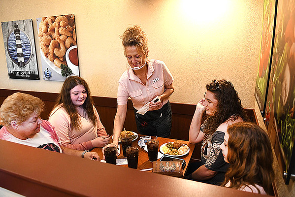 Missy Harmon, shift leader, third from left, serves drinks to, Peggy Kessler, left, Zoey Brrooks, Pamela Brooks and Alyssa Brooks.<br /> (Rick Barbero/The Register-Herald)