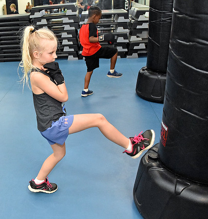 (Brad Davis/The Register-Herald) Six-year-old Sophie Phillips, near, and seven-year-old Mekhi Edwards work on kicks during the first Kids Combat Cardio session to be held Sunday afternoon at the YMCA of Southern West Virginia. The one hour class will be held every Sunday in two age groups, kids 5-10 at 3:00 p.m., kids 11-18 at 4:00 p.m. and combines a fun workout environment with basic mixed martial arts training and techniques.