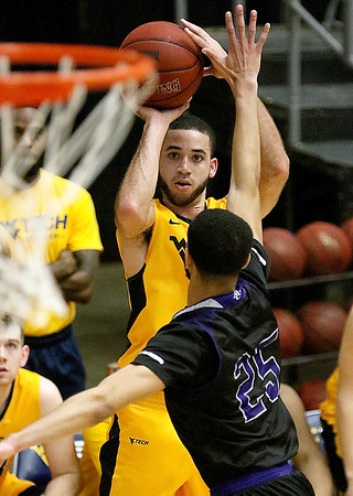 (Brad Davis/The Register-Herald) WVU Tech's Dominik King shoots from three-point range as Asbury's Deion Cochran defends during a comeback victory Wednesday night at the Beckley-Raleigh County Convention Center.