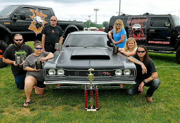 Lester resident Jay Matics, far right, joins his wife Theresa, upper right, and his daughter Nyah, middle right, for a quick photo July 20 during the closing moments of the Friends of Coal Auto Fair at the YMCA Paul Cline Memorial Youth Sports Complex. In the photo with them are Rebecca (far lower left) and James (far left) Bailey, along with Chris Taylor (upper left), Matics' employees at his business, Vigilante Customs. His 1969 Dodge Coronet with a 665 horsepower-producing, 572 cubic inch Hemi engine earned him Participants Pick Best of Show, the fair's top prize. The award was based on participant voting, and his ride will represent next year's auto fair in all promotional materials. Brad Davis/The Register-Herald