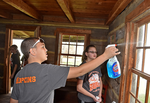 (Brad Davis/The Register-Herald) Bradley Elementary 5th graders and student council members Karhlyle Hopkins, left, and Rachael Wriston clean in the post office in the back yard of Wildwood House during a Spring cleanup Saturday afternoon.