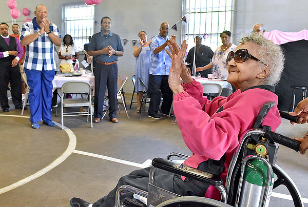 (Brad Davis/The Register-Herald) Friends and family stand and applaud as 100-year-old Loretta Shellow, right, arrives at her birthday party with help from Debra Dozier, one her 5 granddaughters, Saturday afternoon at the Maxwell Hill Community Center.