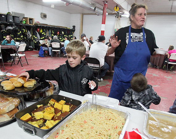 Brad Davis/The Register-Herald Seven-year-old Justin Cadle, left, grabs a roll while Rhodell Volunteer Fire Department chief Patricia Cox, right, shoots the breeze with fellow community members (unphotographed behind camera) during the town's annual Thanksgiving dinner Saturday night.
