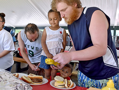 (Brad Davis/The Register-Herald) Four-year-old Kendell Harris stands on the seat of the picnic table to inspect the work as guardian William Richardson, right, prepares hamburgers and hot dogs for her and younger brother Draydon, 2, who can be seen below trying to peek in on the progress during the 14th Annual Juneteenth Community Cookout Sunday afternoon at New River Park.