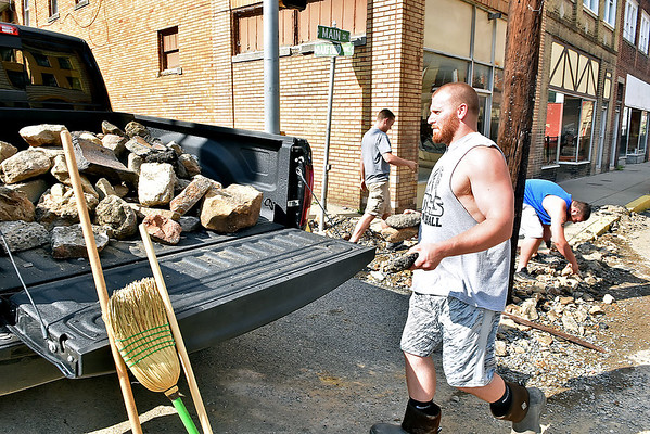 (Brad Davis/The Register-Herald) Resident Gary Roach carries another large rock to the back of a truck as J.J. Johnson, left, and his brother Jarron help to pick up larger pieces of rock and concrete debris during cleanup efforts Saturday in Richwood.