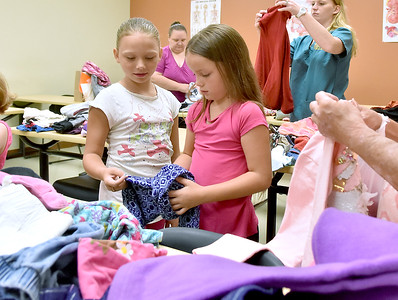(Brad Davis/The Register-Herald) Seven-year-old Isabella Hodge, right, and nine-year-old Emily Worix pick out clothes during Valley College's Day of Caring Saturday afternoon on the Beckley Campus. The event provided clothing, shoes, backpacks and school supplies to kids between the ages of four and 17, and food items to their families.