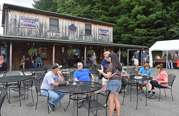 (Brad Davis/The Register-Herald) Attendees relax at tables, while others hunker under the porch due to occasional rain sprinkles on the grounds of Kirkwood Winery Sunday afternoon.