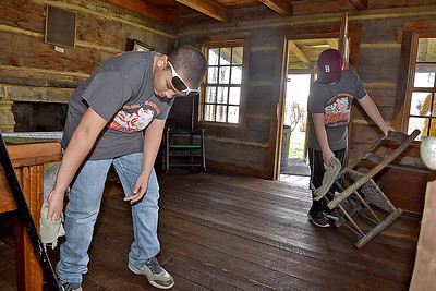 (Brad Davis/The Register-Herald) Bradley Elementary 5th graders and student council members Karhlyle Hopkins, left, and Blake Nixon clean in the post office in the back yard of Wildwood House during a Spring cleanup Saturday afternoon.