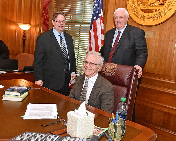 (Brad Davis/The Register-Herald) Rocket Boy Homer Hickam gets an idea of what the view is like from governor Jim Justice's seat inside his office at the conclusion of a meeting between him, Theatre West Virginia's Scott Hill (unphotographed) and Allen Media Strategies' Burke Allen, left, Monday afternoon in Charleston.