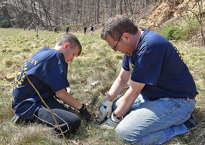 (Brad Davis/The Register-Herald) Jorn Otte, right, and his 13-year-old son Caleb join with around 60 fellow Rotarians from 10 different chapters around the state in planting 1,400 oak, various pine and hybrid chesnut trees Saturday morning at the Bechtel Summit Reserve.