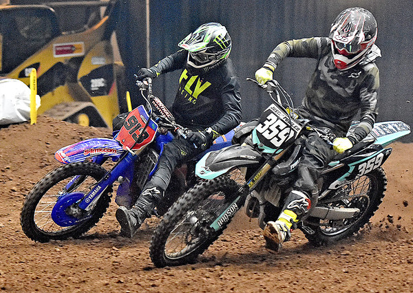 (Brad Davis/The Register-Herald) Fayetteville's Shawn Laughery, left, battles for position with Rush Kentucky's  Justin Fowler during the weekend's Tristate MX dirt bike racing event Saturday night at the Beckley-Raleigh County Convention Center.