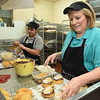 Sargat Dahal Thapa, left, and Lynn Plumley, putting final touches on donuts at the Donut Connection<br /> (Rick Barbero/The Register-Herald
