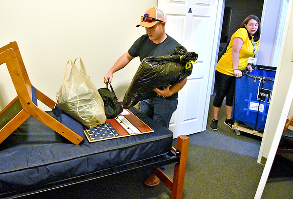 (Brad Davis/The Register-Herald) Incoming WVU Tech student Kevin Morris carries belongings into his dorm at University Hall as current student and volunteer Jessica Beck helps out during move-in day Sunday morning.
