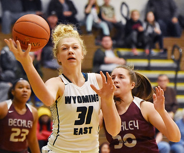 Wyoming East's Emily Saunders hauls in a passes Woodrow Wiloson's (30) defends  during their basketball game Wednesday in New Richmond. (Chris Jackson/The Register-Herald)