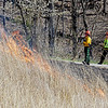 Crew members with the Beckley Fire Department and NPS watch as the NPS conducts a prescribed burn at the Sandstone Visitor Center as part of the New River Gorge National River Thursday. The annual burn was slower this year to let more wooded invasive species of plants burn away, said Dave Bieri, with the NPS. (Chris Jackson/The Register-Herald)