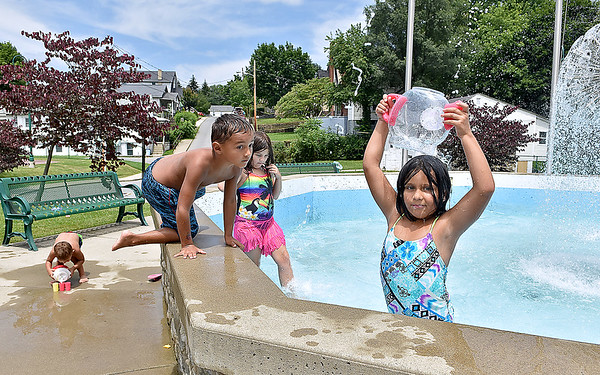 (Brad Davis/The Register-Herald) No swimming pool nearby? No problem for youngsters (from right) Ava, 7, Alana, 9, Luis, 5, and Brayden Delorso, 4, took advantage of the cool waters flowing in the fountain at the Thornhill Courts park along 2nd Street Friday afternoon. With temperatures around 90 again, anything nearby that funtioned as a massive sprinkler, such as the 2nd Street Park's fountain, was bound to draw anyone looking to stay cool through the day.