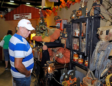Brad Davis/The Register-Herald Clear Creek resident Kenneth Painter looks over craft items available at The Carpenter's Loft booth inside the Beckley-Raleigh County Convention Center Saturday afternoon during the Appalachian Arts & Crafts Fair.