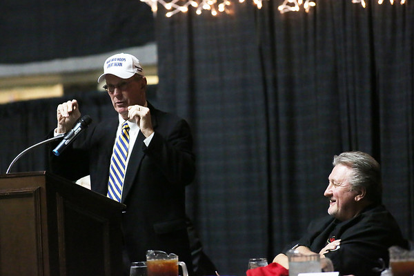 """Charlie Houck speaks while wearing a hat that reads """"Make West Virginia Basketball Great Again"""" as West Virginia University Men's Basketball Head Coach Bob Huggins laughs during the 32nd Annual Spirit of Beckley Awards Presentation at the Beckley-Raleigh County Convention Center in Beckley on Monday. (Chris Jackson/The Register-Herald)"""