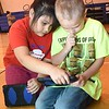 "Shylah Aquino, left, helps Noel Bragg, second graders, during a Legacy Lab class at Cranberry-Prosperity School. Cranberry Prosperity has been awarded with the status of being an ""Apple Distinguished School"" for being top notch with technology use in their classrooms.<br /> (Rick Barbero/The Register-Herald)"