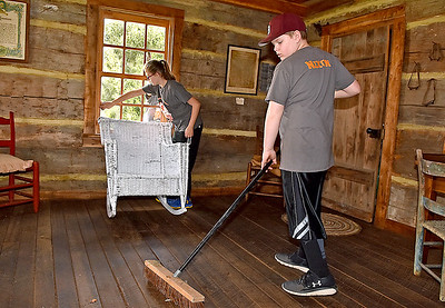 (Brad Davis/The Register-Herald) Bradley Elementary 5th graders and student council members Blake Nixon, right, and Rachael Wriston clean in the post office in the back yard of Wildwood House during a Spring cleanup Saturday afternoon.