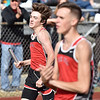 (Brad Davis/The Register-Herald) Oak Hill's Ian Bibb crosses the line in first for his team in the 4x800 meter relays as teammate Mason Harp (foreground) cheers him on from the infield during the Dickey's Invitational Friday afternoon at Independence High School.