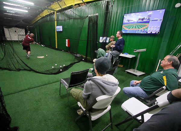 Brad Davis/The Register-Herald Folks watch the action as Woodrow Wilson's Michael Maiolo bats during Upper Deck indoor hitting league action Sunday afternoon in Beckley.