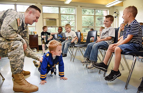 Wesley Bowling, Army National Guard Specialist, assists Bryson Acord, pre-k student, with doing pushups during the schools Career Day. Bowling demostated and spoke with the students about some of his traingng with the National Guard. Nine other vendors also participated and students rotated every 10 minutes to hear them speak about their careers. (Rick Barbero/The Register-Herald)