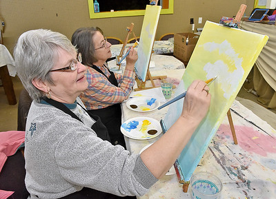 "(Brad Davis/The Register-Herald) Mt. Hope residents Ramona Brown, near, and Dolly Lilly spend a Sunday painting what will eventually be a scene of hot air balloons in an afternoon sky using acrylics on canvas during a studio painting session at 110 Marshall in Beckley. Painting sessions are often themed in a variety of ways designed to help painters build skills in painting certain types of objects or textures, with yesterday's being ""Up, Up an Away"" in reference to the balloons. Similar upcoming painting events will be ""Peaceful River"" on Monday, March 27 at 6:00 p.m. and ""Angel Wings"" Friday, April 7 at 6 p.m. Keep an eye on their facebook page or give them a call at 304-634-8367."