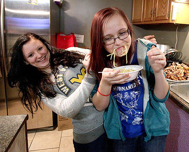 Brad Davis/The Register-Herald Young Rhodell resident Kristen Smith, 13, tries to enjoy some pasta as her slightly camera-shy friend Ashlea Sargent, 14, tries to use her as a shield as the two enjoy the town's annual Thanksgiving dinner Friday night.