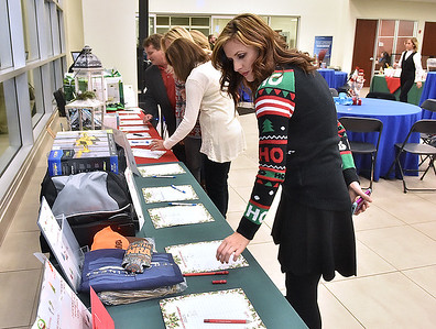 (Brad Davis/The Register-Herald) Attendees browse silent auction items at the Mountaineer Automotive silent auction and Christmas fundraising party for Mac's Toy Fund Thursday night inside the showroom of the Eisenhower Drive dealership.