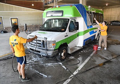 Santiago Cruz, left, and Cameron Underwood, WVU Tech students, washes one of the New River Transit buses in the parking garage on Prince Street in Beckley Tuesday morning. Students volunteered hundreds of hours at multiple service sites on Tuesday, Volunteers served at nearly 20 sites over the course of five hours. Notable projects include cleaning and prepping WV HIVE's new expansion site at the Beckley Presbyterian Church; cleaning buses and assisting on ride-alongs with the Raleigh County Community Action Association and New River Transit Authority; and trail cleanup at Little Beaver State Park.  (Rick Barbero/The Register-Herald)