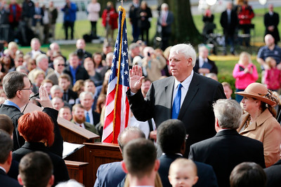 Governor Jim Justice takes the oath of office from Chief Justice Allen H. Loughry II as the 36th Governor of the State of West Virginia as his wife Cathy looks on at the Capitol in Charleston on Monday. (Chris Jackson/The Register-Herald)