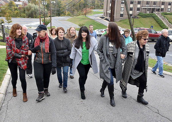"""(Brad Davis/The Register-Herald) A group of friends and family led by his wife Tammy (middle in green), son Chris (behind Tammy at left) and daughter Ann Elizabeth (right of Tammy), among others, make their way up what's now known as Mel Hancock Way prior to a brief ceremony for the late Beckley resident Saturday afternoon. Several friends and relatives of Mel's attended a brief and somber ceremony as they and mayor Rob Rappold paid tribute by renaming """"A"""" Street after him."""