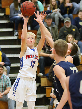 (Brad Davis/The Register-Herald) Midland Trail's Austin Isaacs shoots from three-point range as Greenbrier West's Noah Midkiff defends Friday night in Hico.