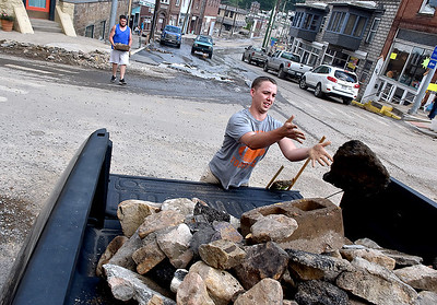 (Brad Davis/The Register-Herald) Resident J.J. Johnson throws another large rock into the back of a truck as his brother Jarron (background upper right) follows during cleanup efforts Saturday in Richwood.
