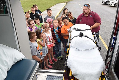 Jimmy Lilly, emt Best Ambulance, pulls the stretcher out of his ambulance and talked about his job to third grade students at Lester Elementary School during the schools Career Day. Total of ten vendors participated and students rotated every 10 minutes to hear them speak about their careers. (Rick Barbero/The Register-Herald)