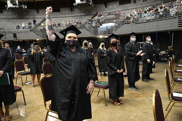 Erica Hardwick, of Bluefield, raises her arm after graduating from New River Community & Technical College at the Beckley-Raleigh County Convention Center Saturday morning.<br /> (Rick Barbero/The Register-Herlad)