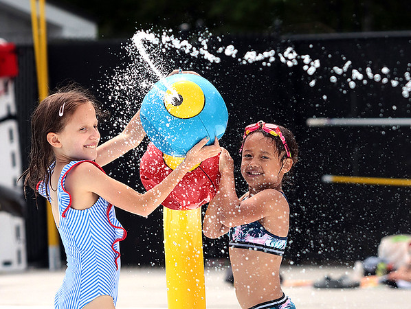 Maya Walter, 9, and Laykin Dufalla, 7, play with a water fountain at the new White Sulphur Springs City Pool Wednesday. The previous pool had been closed for almost eight years and the new pool, which opened Memorial Day weekend includes a Wellness Center and a water slide. Jenny Harnish for the Register-Herald