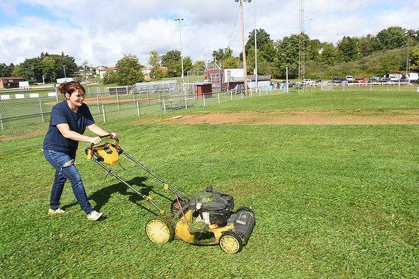 VAnessa McGlothlin, behavior support specialist ResCare, cutting grass on field 5 at Beckley Little League off Eisenhower Drive. ResCare is a behavior Health Agency that provides residential services for people with intellectual disabilities. The agency picked Beckley Little league for their give back to the community project by providing a combined thirty employees and residents to spruce up five fields.<br /> (Rick Barbero/The Register-Herald)