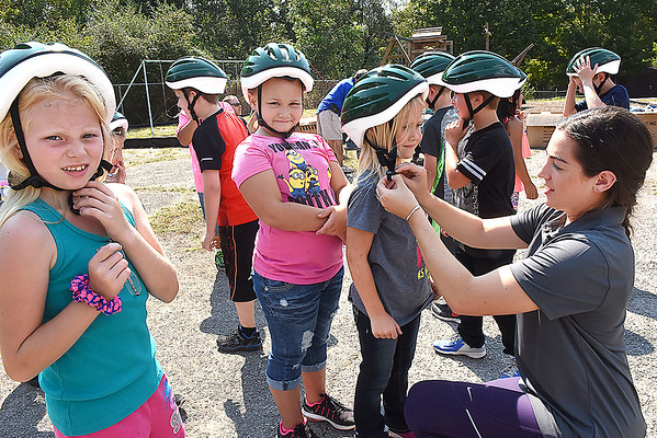 Malorie Polster, community health director Active Southern West Virginia, right, shows childern in Tammy Darnell's second grade class at Mt. Hope Elementary School, how to properly strap helmets on before riding a bike during a bike saftely rodeo.  (Rick Barbero/The Register-Herald)