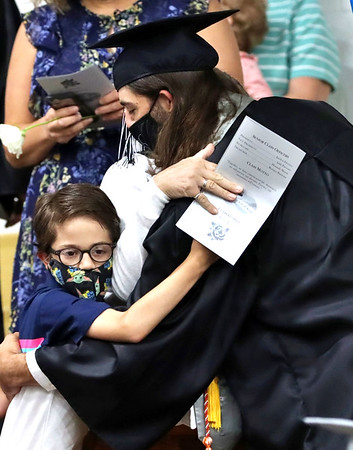 Spencer Kenney hugs his family during the Westside High School graduation flower ceremony.<br /> Jim Cook for the Register-Herald