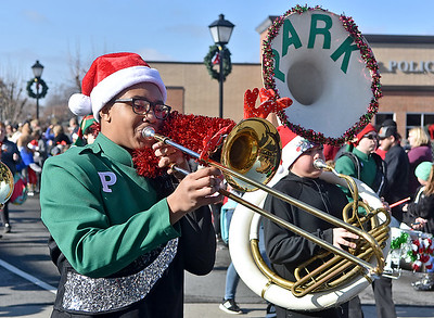 (Brad Davis/The Register-Herald) Members of the Park Middle School marching band perform along Neville Street with their instruments decorated for the season during the Beckley Christmas Parade Saturday morning.